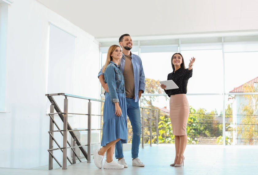 Female real estate agent showing new house to couple, indoors.